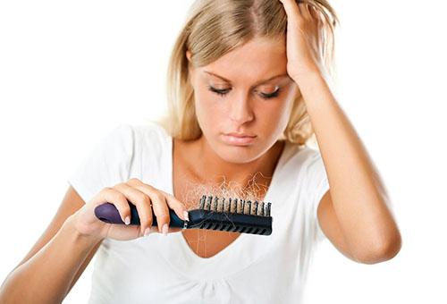 Женщина смотрит на расческу с выпавшими волосами