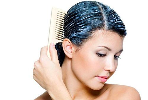 Женщина расчесывает волосы с нанесенной на них маской