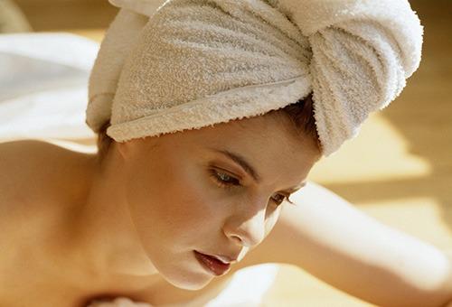 Женщина с обернутыми полотенцем волосами