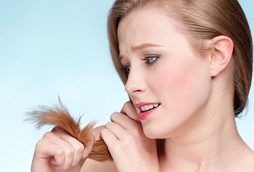 Девушка недовольна ломкими кончиками волос