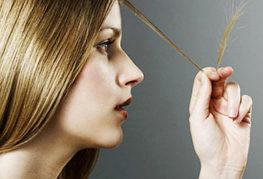 Девушка смотрит на секущиеся кончики волос