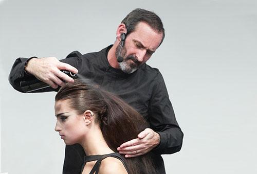 Стилист наносит лак на волосы модели