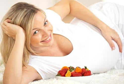 Беременная женщина с тарелкой фруктов и ягод